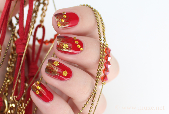 Red nails with golden rhinestones
